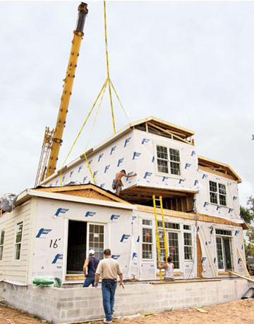 This picture shows a module being lowered in place by a crane. With modular  building, the house is constructed in separate box-like modules which are  then ...