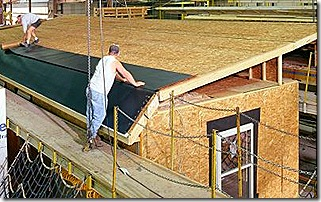 Workers roofing a modular home in the factory